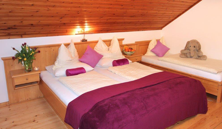 bedroom with double bed, bedside table with flowers and fruits, single bed with a soft toy