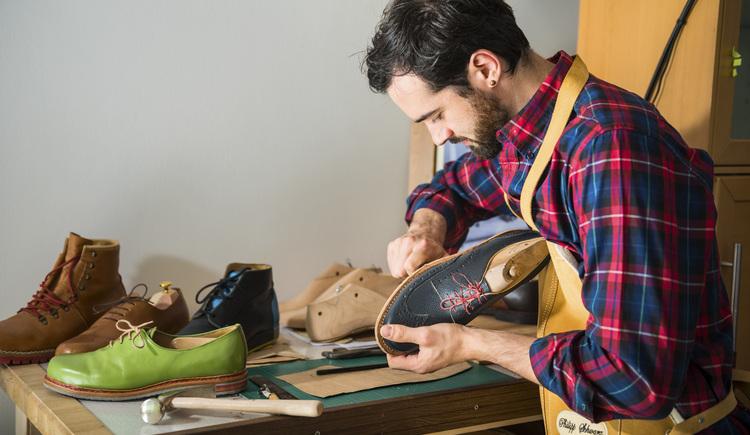 Der Schuhmacher der Goiserer Schuhe Philipp Schwarz bearbeitet einen Goiserer Halbschuh in seiner Werkstätte. (© Marc Schwarz - marcschwarz.at)