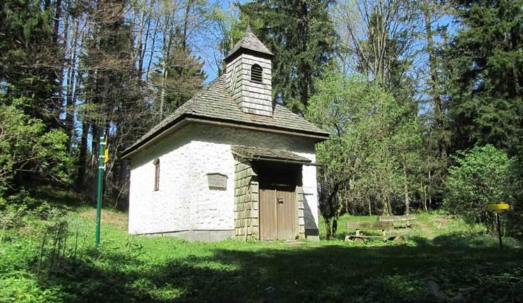 kleine Kapelle auf einer Lichtung im Wald, umringt von Wegen und Bäumen
