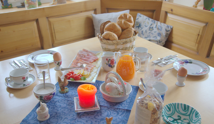 Breakfast table with rolls, eggs, ham, cheese,. coffee and orange juice