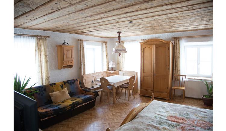 Wohnbereich mit Couch, Eckbank Tisch mit Stühle, Schrank, Fenster