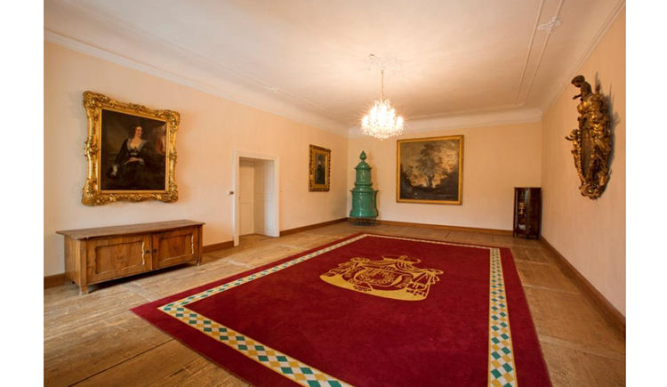 Palatial room with large paintings on the wall, old chest of drawers, large carpet