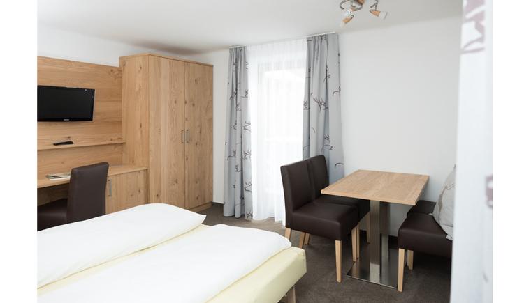 Doppelbett, Tisch mit Stühlen, seitlich ein Kleiderschrank, Stuhl, Fernseher an der Wand, im Hintergrund eine Balkontür