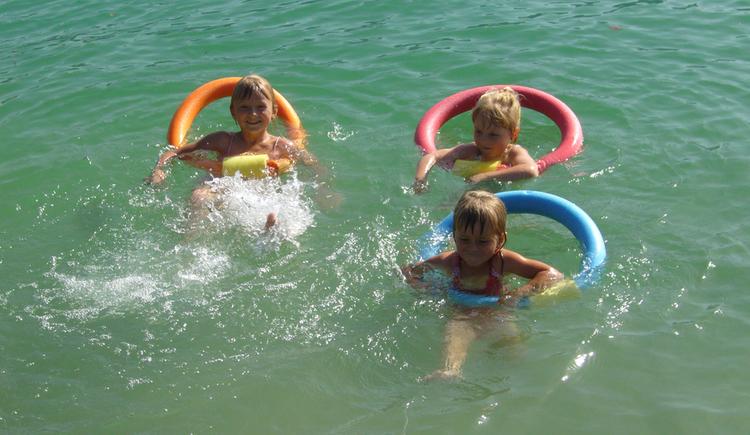 children with pool noodles in the lake