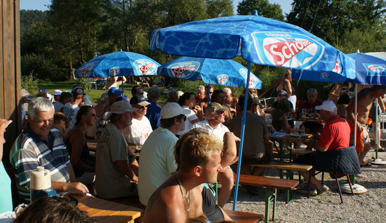 persons are sitting at tables under sunshade\n