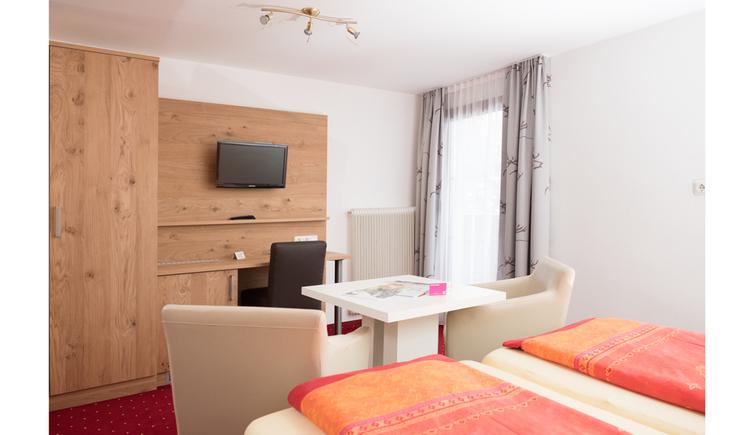 Schlafzimmer mit Doppelbett, Tisch und Stühle, im Hintergrund ein Kleiderschrank, Fernseher an der Wand, seitlich eine Balkontür
