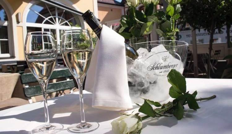 2 Sektgläser und eine gekühlte Flasche Sekt auf einem Tisch mit einer Rose, im Hintergrund der Gastgarten. (© Hotel Restaurant Krone)