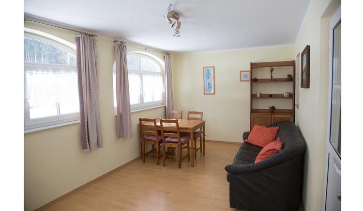 Wohnbereich mit Couch, Tisch und Stühle, Fenster seitlich