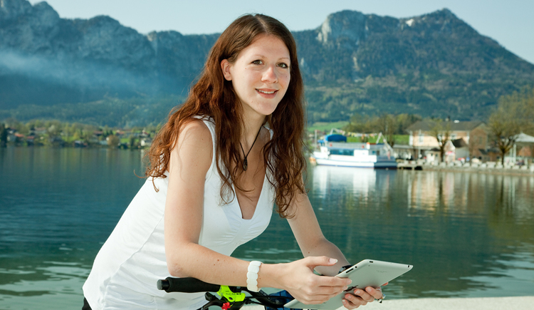 Person with a tablet, in the Background a lake, ship and mountains