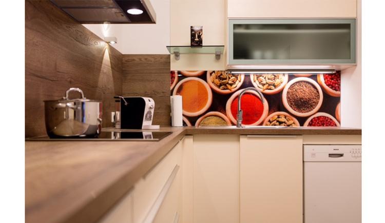 Blick in die Küche, am Herd steht ein Topf, Kaffeemaschine, Geschirrspüler