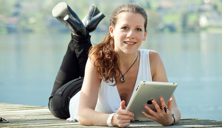 Person liegt am Steg mit einem Tablet, im Hintergrund der See