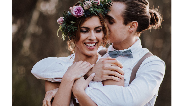 Blick auf ein Brautpaar, Blumen in den Haaren. (© Alexandra Fazan)
