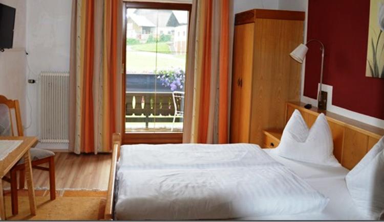 Doppelbett, dahinter ein Schrank, seitlich Tisch mit Stuhl, im Hintergrund befindet sich eine Balkontüre