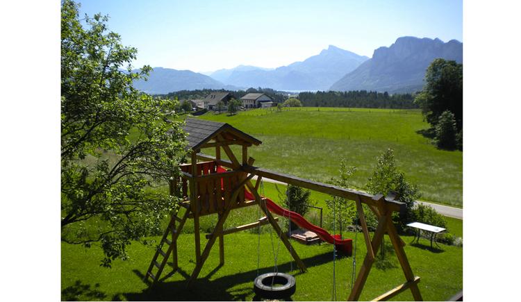 Rutsche, Reifenschaukel, Sandkiste - stehen in der Wiese, im Hintergrund die Landschaft und die Berge