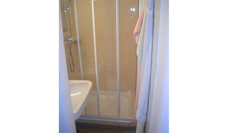 Bathroom with shower, side washbasin and towels hanging on the wall