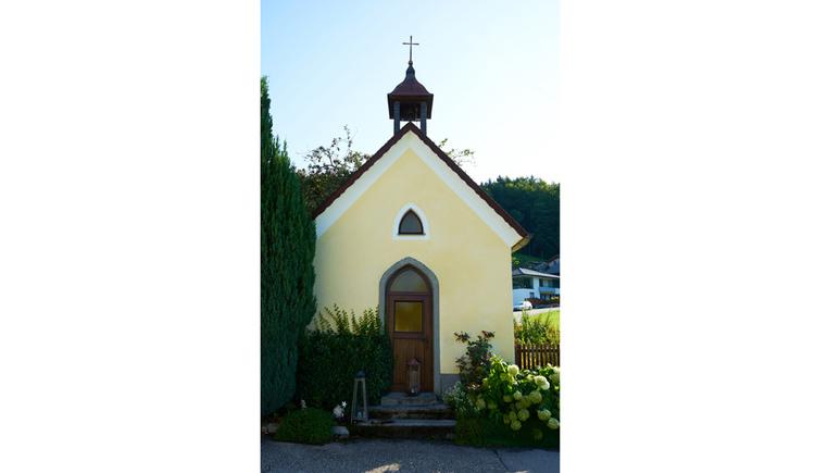 Blick auf die Kapelle, im Vordergrund Pflanzen, seitlich ein Baum