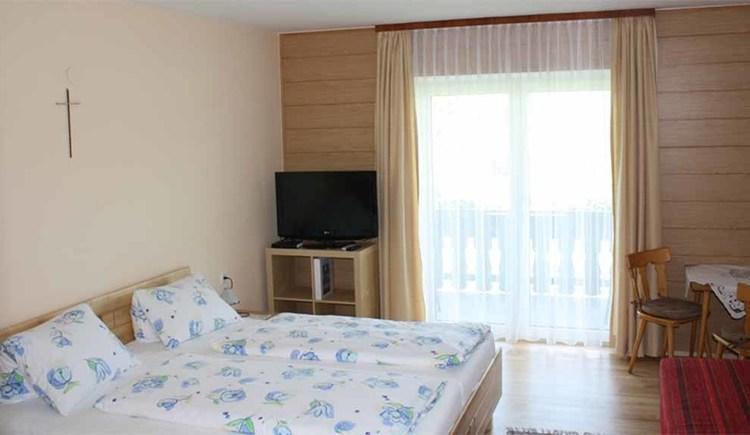Zimmer mit Doppelbett im Hintergrund ein Fernseher und eine Balkontür