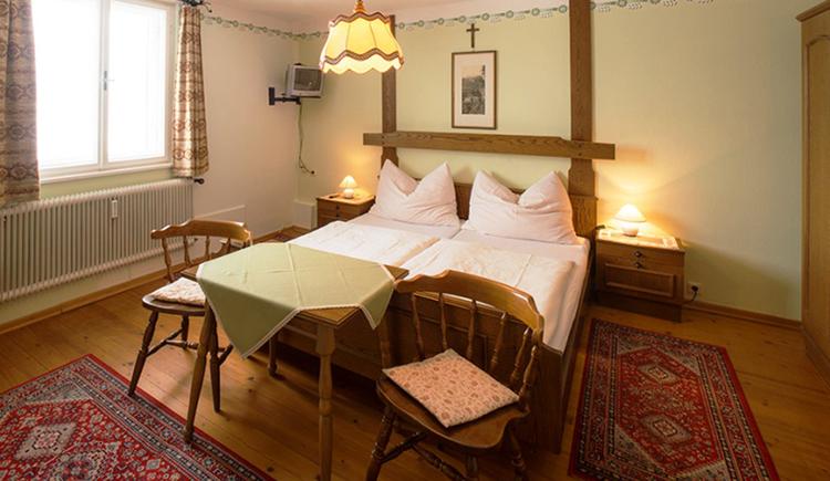Schlafzimmer mit Doppelbett, Nachtkästchen, mit Tischlampe, Tisch und Stühle, seitlich ein Fenster