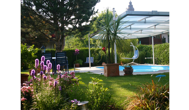 View of the swimming pool, hanging chair, meadow, shrubs