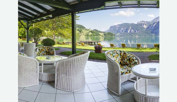 View from the lake terrace with wicker chairs, tables, on the meadow deck chairs by the lake, in the background the mountains. (© Hotel Seehof)