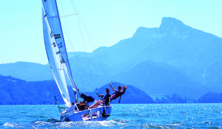 Sailing boat with some persons on it, in the background there is the mountain Schafberg. (© Segelschule Mondsee)