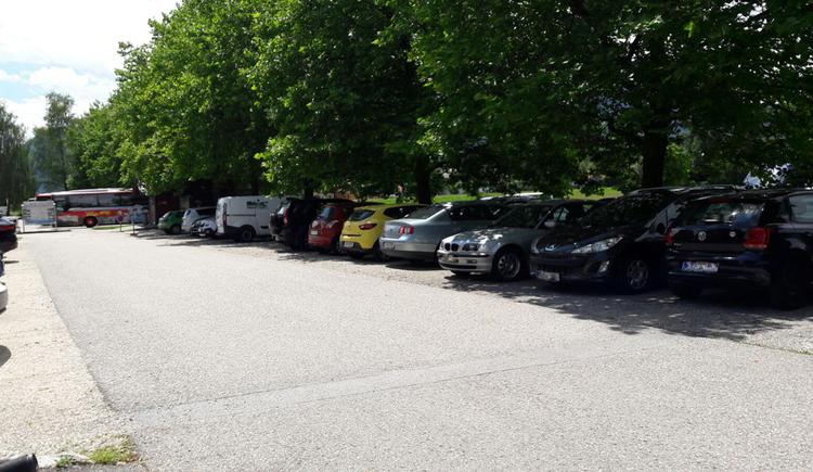 Parkende Autos, im Hintergrund Bäume