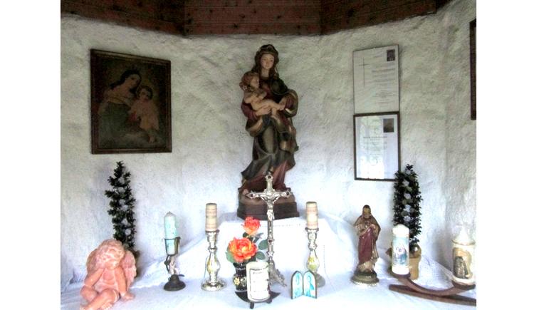Blick auf den Altar mit Heiligenfigur, Kerzen, Bilder an der Wand