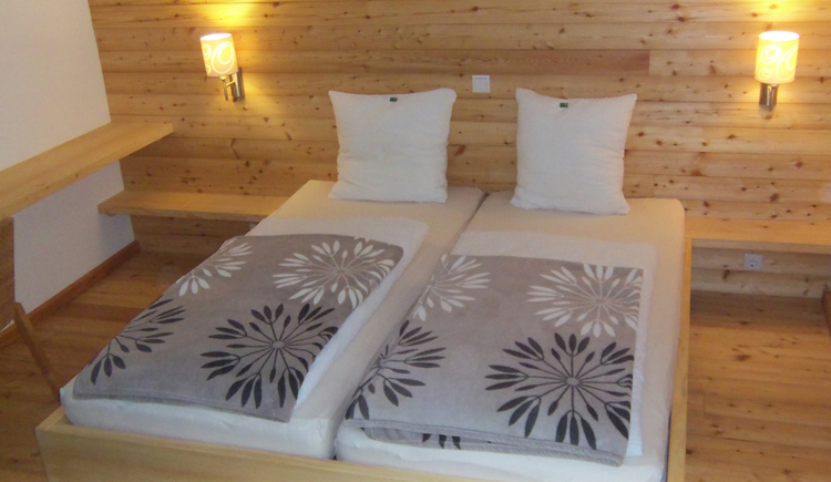 bedroom with double bed, wooden wall with lamps\n