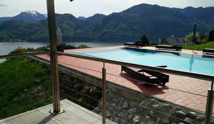 view of the terrace on the pool with sun loungers, in the background lake and mountains\n