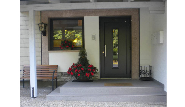Entrance to the house, with a bench and flowers
