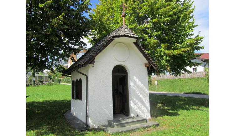Blick auf die Kapelle in einer Wiese, im Hintergrund Bäume