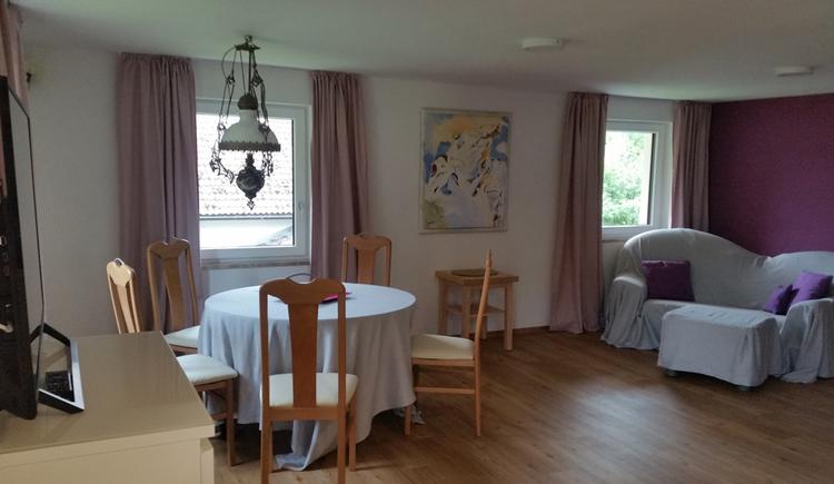 Tisch mit Stühlen, im Hintergrund seitlich eine Couch, Fenster