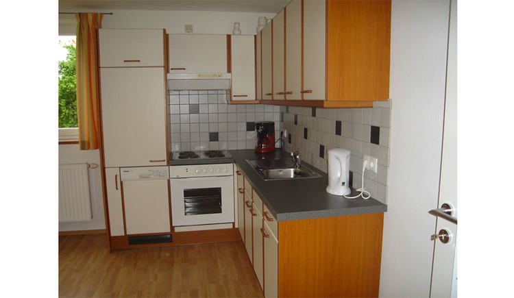 Kitchen with dishwasher, stove, coffee machine, sink, water cooker, in the background a small part of the window