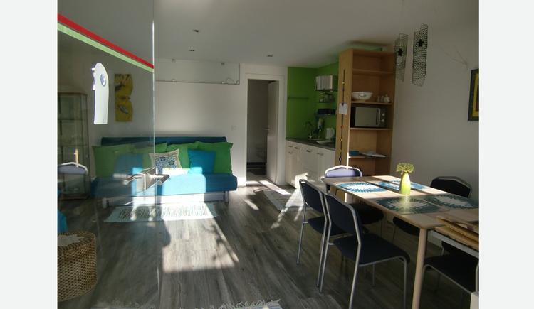 seitlich ein Tisch mit Stühle, im Hintergrund seitlich eine Küche, im Hintergrund Couch mit Polster