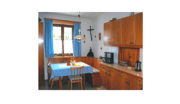 kitchen with water cooker, coffee machine, in the background the dining area with corner bench, table and chairs, window