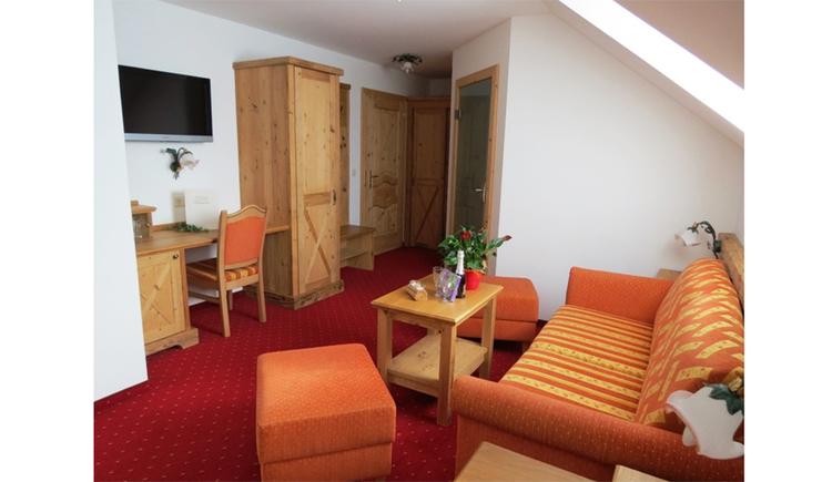 Wohnbereich mit Couch, Tisch und Hocker, im Hintergrund Schreibtisch mit Stuhl, darüber ein Fernseher, Kleiderkasten