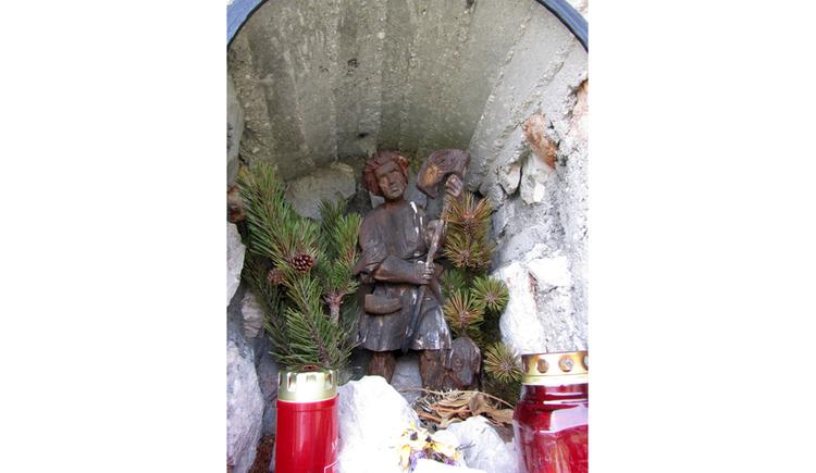 Blick auf eine Heiligenfigur, im Vordergrund Kerzen
