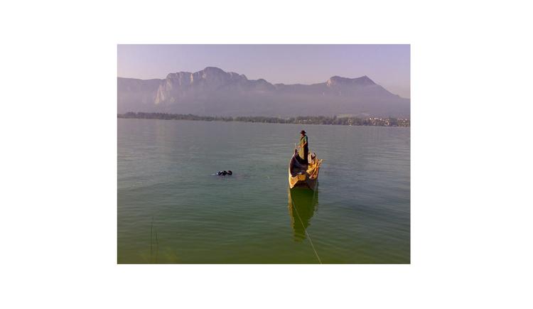 Blick auf den See, Person stehend in einem Boot, im Hintergrund die Berge