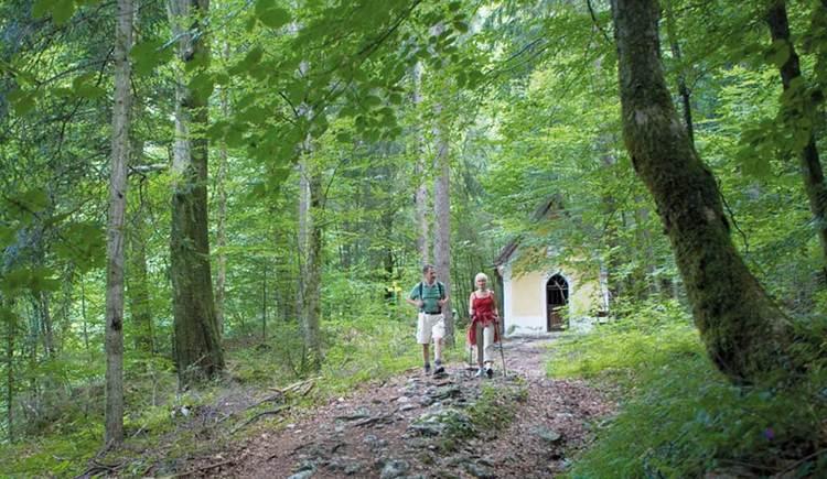 Blick auf eine Frau und ein Mann, das einen Weg im Wald entlang geht, im Hintergrund eine kleine Kapelle