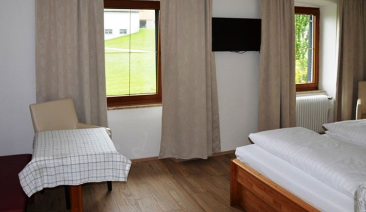 bedroom, on the side a small part from the double bed, table with chair, in the background are windows\n