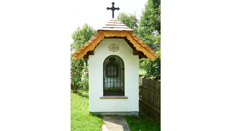 Blick auf die Kapelle, hinter dem Gitter ein Gemälde, am Dach befindet sich ein Kreuz