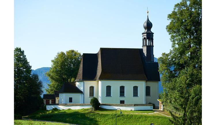 Blick auf die Kirche, im Vordergrund Wiese, seitlich Bäume