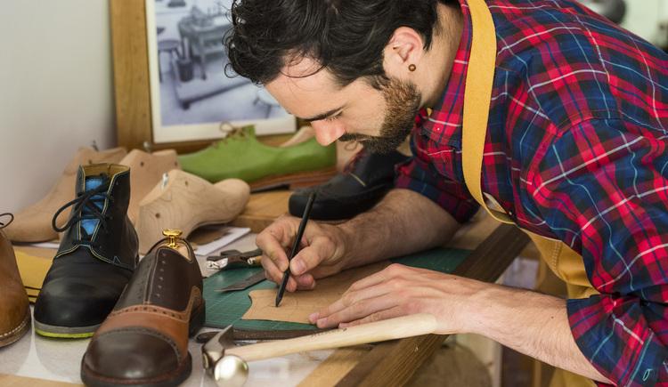 Der Goiserer Schuhmacher Philip Schwarz zeichnet eine Vorlage in seiner Werkstätte. (© Marc Schwarz - marcschwarz.at)