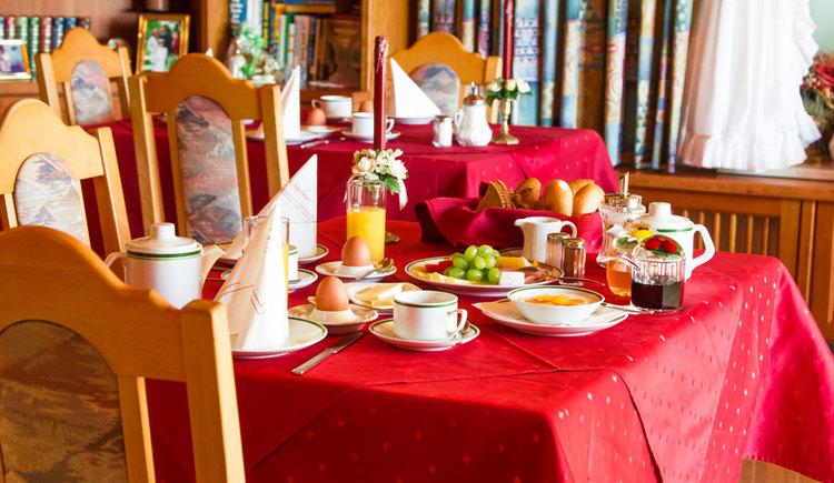 gedeckter Tisch zum Frühstück, mit Eier, Weintrauben, Wurst, Käse, Butter, Orangensaft, Marmelade, Sessel