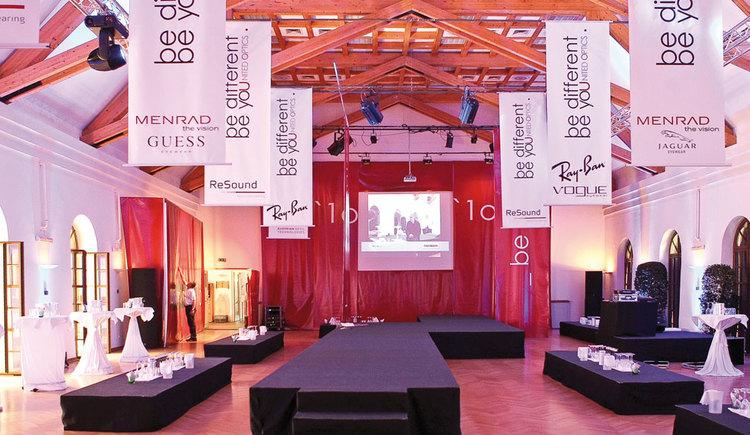Veranstaltungszentrum SALA Schloss Mondsee mit Bühne, Werbebannern, die von der Decke hängen und Technikequipment