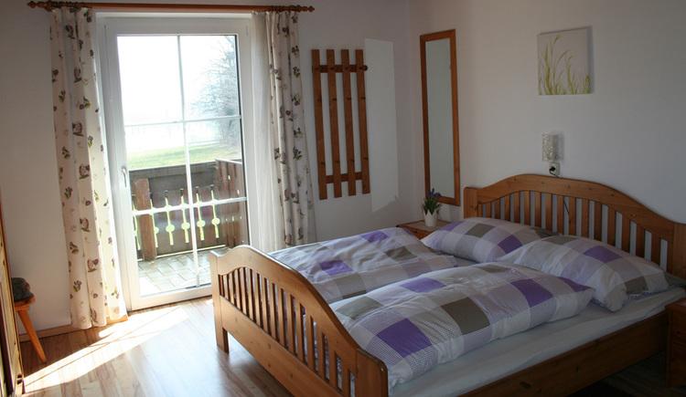 Schlafzimmer mit Doppelbett, Spiegel, kleiner Gaderobe an der Wand, seitlich Blick auf den Balkon durch die Tür