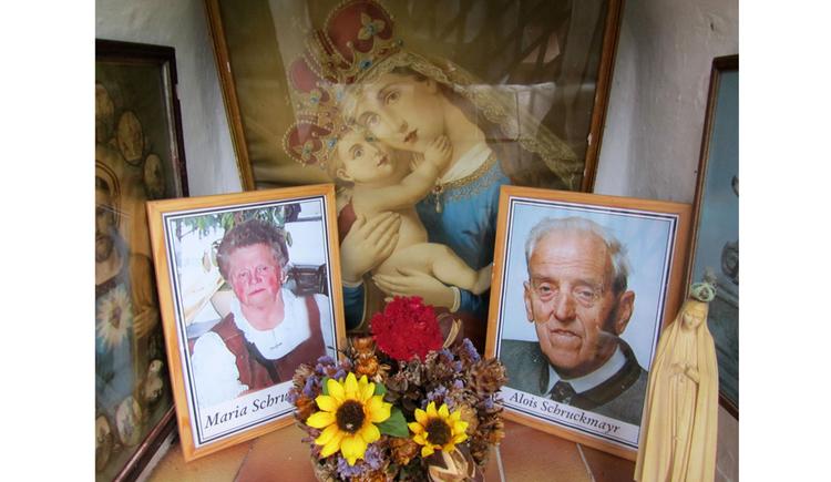 Fotos im Rahmen, Blumen, im Hintergrund ein Marienbild, seitlich eine Marienstatue