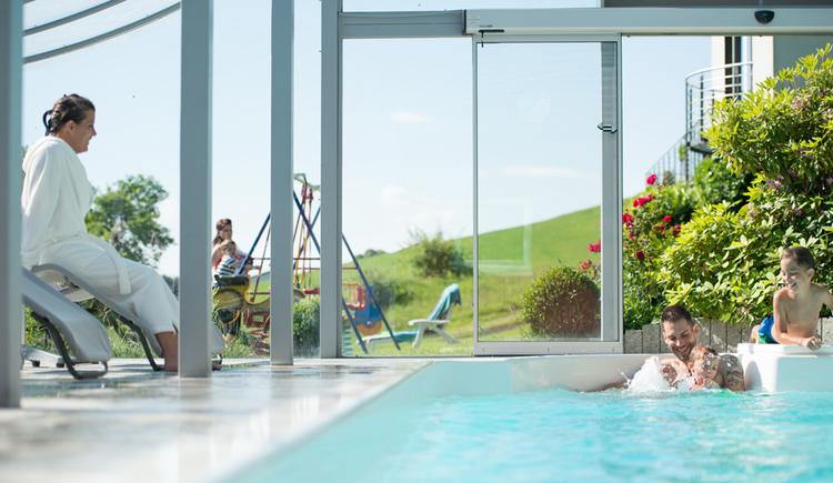Schwimmbad mit Familie im Wasser, im Hintergrund draußen Schaukel mit Liegestuhl