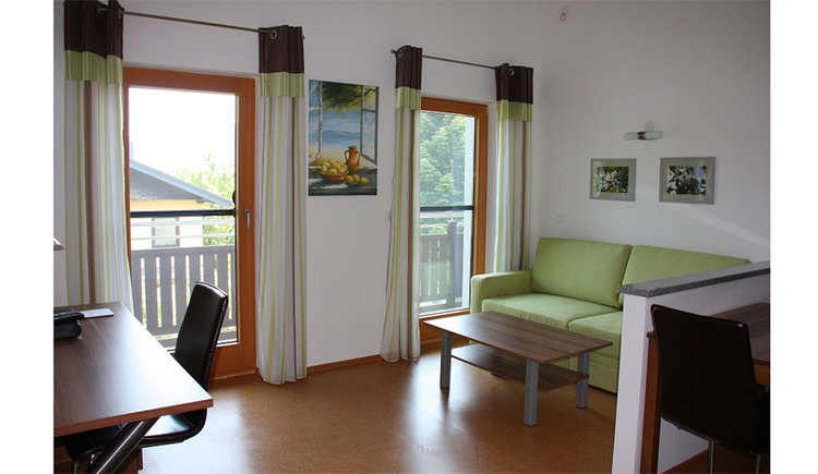 couch with table on the side, desk with chair on the over , balcony doors in the background