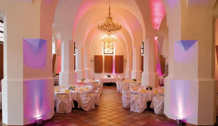Säulenhalle im Veranstaltungszentrum SALA Schloss Mondsee mit festlich geschmückten Tischen. (© Sala Schloss Mondsee)